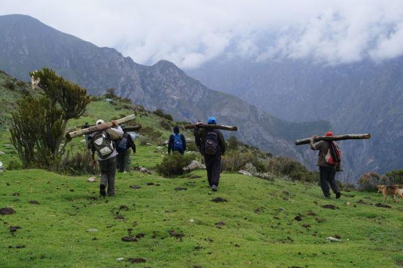 Miembros de la comunidad de Miraflores transportando postas para construir cercas en el área donde el agua traída por el canal les permitió restaurar los pastos y mejorar la rotación de ganado.